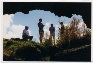 Team members framed by the mouth of a sheltering cave